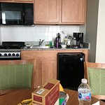 full kitchen with microwave, coffee maker, stove top, fridge