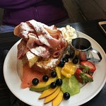 French Toast complete with bacon, maple syrup, cream and fresh fruit.