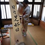 Wakaba-san showing her own calligraphy hanging scrolls