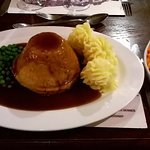 Steak pudding with piped mashed potatoes and selectioon of fresh vegetables