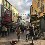 Irish musicians busking at a lively intersection in the Latin Quarter.