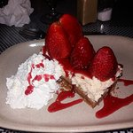 Homemade New York cheesecake topped with fresh Strawberries.
