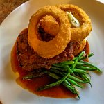 Meatloaf over garlic mashed potatoes and asparagus in a sherry sauce gravy with Onion Rings