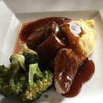 Roasted lamb rump w/ redcurrant & thyme gravy w/ dauphinoise potatoes & seasonal greens