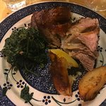 Roast suckling pig with potatoes and spinach