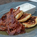 Homemade pancakes with maple syrup and crispy bacon