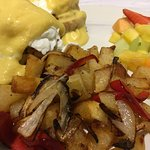 Crab Benedict with fried potatoes and fresh fruits