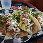 Catrinas pork tacos on soft flour tortillas with toppings