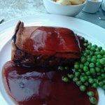 Huge slab of steak pie with chips, peas and gravy