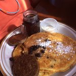Blueberry pancakes with hot warmed syrup and patty sausage