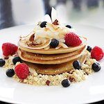 Home-made coconut flour pancakes blueberry compote, fresh berries, pecan crumble and whipped Gre