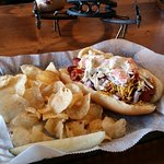 "Our "" kitchen sink dog "" all beef dog topped with chili, cheese, onions, slaw and bacon. Also of"