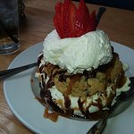 Cookie dessert with whip cream topped with strawberries drizzled with chocolate sauce