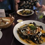Hot seafood platter (front) and shellfish pasta with bread basket