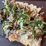 crispy flatbread with mushrooms, nuts and delicate greens