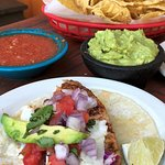 Fish Taco- Grilled fresh fish, slaw, tomatoes, onion, cilantro, avocado & lime.