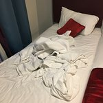 Unmade bed with dirty towels left behind