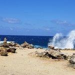 Waves crashing on the rock beach near natural bridge.