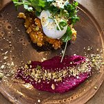Poached egg on pumpkin and feta on nut bread with beetroot purée and nuts with rocket