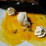en dessert un carpaccio d'ananas avec un coulis de mangue une boule de glace