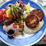 salmon cakes over sauce with salad and cole slaw