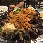 tábua com camarão, lula, isca de peixe e mariscos