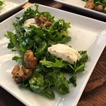 Arugula and goat cheese salad dusted with peppercorn and walnuts