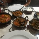 The selection of dishes - fish curry on the left, various veggie sides on the right