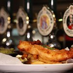 Battered haddock and chips, served with mushy peas and homemade tartar sauce.