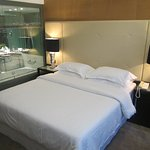 The bed in the room, bathroom behind glass