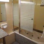Salle de bain avec baignoire balnéo et petits produits d'hygiène.