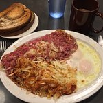 Eggs with corned beef hash, hash brown potatoes and rye toast.