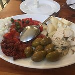 Cheese platter with tomatoes, onion and olives