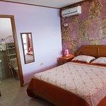 Habitación matrimonial con cama queen , mini nevera y balcón vista al mar