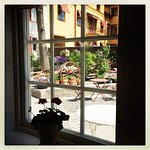 En utrolig hyggelig café med sjarmerende bakgård, full av herlige blomster og grønne vekster.