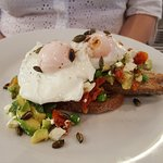Avocado, poached eggs, feta, sun-dried tomatoes, peas and pumpkin seeds on sourdough toast