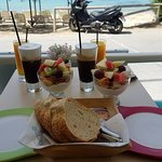 Breakfast spread while sitting at a beachfront table. Greek yogurt with honey and fruit.