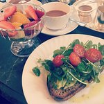 Crushed avocado and tomato on toast, fruit salad and tea with soy milk