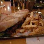 Sandwiche de bondiola (cocinada en cerveza negra) con rúcula, cebolla caramelizada, mostaza y mi