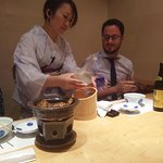 Japanese servers wearing kimono, serving sake.