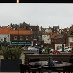 View from the restaurant's bay window showing outside seating and shops across the road.