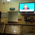 At the counter of the bar watching news