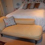 breites, bequemes Bett mit davorstehender Chaiselongue