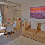 Sunny Seaview Deluxe Suite with sofa bed, kitchenette and cafe table overlooking the waves