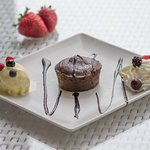 Chocolate coulant with sauce, ice cream, whipped cream, fruits