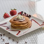 Pancake with nutella, whipped cream, sauce, fruits