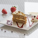 Carrot cake with sauce and whipped cream with fruits