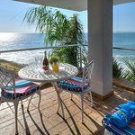 Ocean view of Seaview Luxury Suite balcony with BBQ, lounger and dining suite
