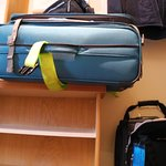 This 24 inch suitcase is hanging over the edge of the luggage rack.h