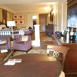 Partial view of living room, large sofa, chairs & tables, desk w/ charging station, 4-seat table